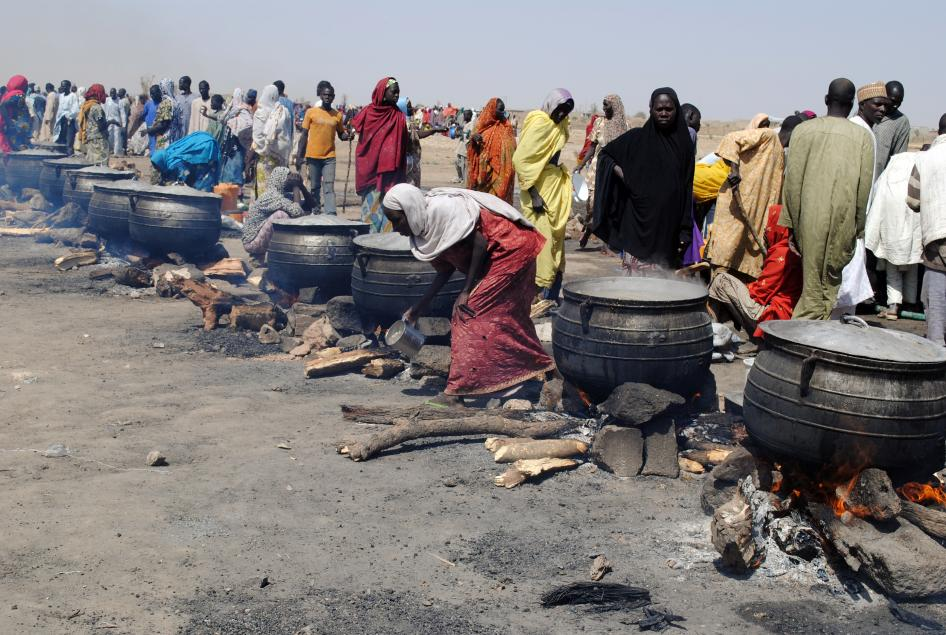 Women cook in pots heated up with firewood at an Internally Displaced Persons (IDP) camp at Dikwa in Borno State, north-eastern Nigeria, on February 2, 2016. © 2016 Getty Images